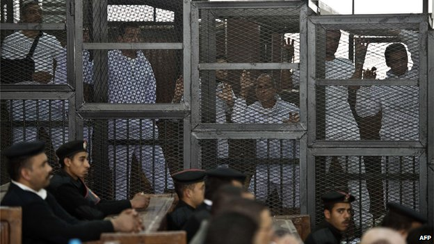 Peter Greste, Mohammed Fadel Fahmy and Baher Mohammed in a cage in court, Cairo (March 2014)