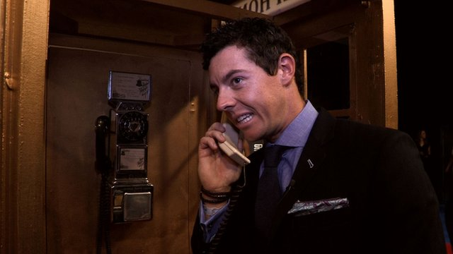 Rory McIlroy on a phone in a phone box