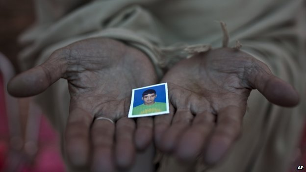 Pakistani Sayed Shah, shows a picture of his son Zulqarnain, 17, a student who was killed in last Tuesday's Taliban attack on a military-run school, in Peshawar, Pakistan, Thursday, Dec. 18, 2014.