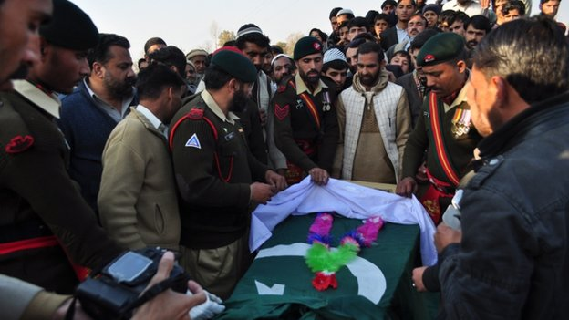 Pakistani army personnel gather around the coffin of army soldier who was killed in the school attack, during a funeral in Mansehra on December 17, 2014.