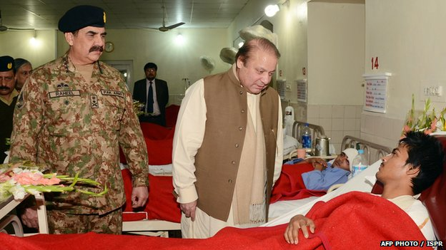 Pakistani Prime Minister Nawaz Sharif (C) talks to an injured student at the military hospital in Peshawar, as army chief General Raheel Sharif (L) looks on.