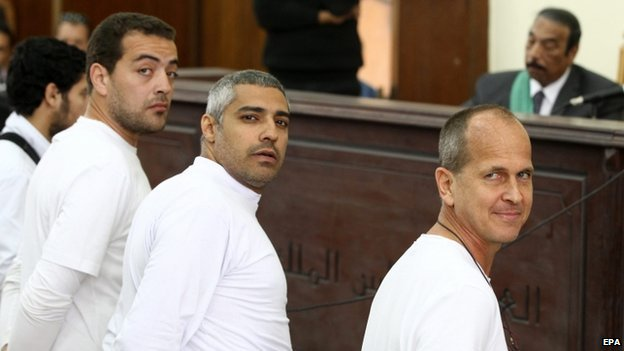 "Australian journalist Peter Greste (R), Canadian-Egyptian journalist Mohammed Fahmy (C) and journalist Baher Mahmoud (L) standing in front of the judge""s bench during their trial on 31 March 2014"