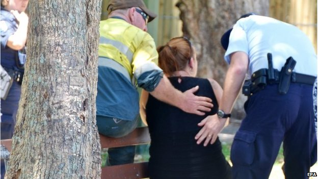 Police comfort a woman outside the house in Cairns (19 Dec 2014)