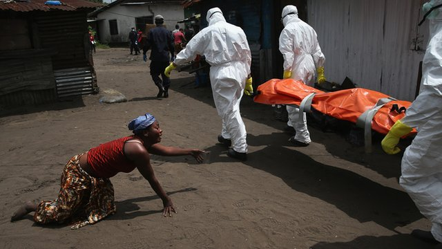 A woman crawls towards the body of her sister as Ebola burial team members take her body for cremation, Monrovia, Liberia