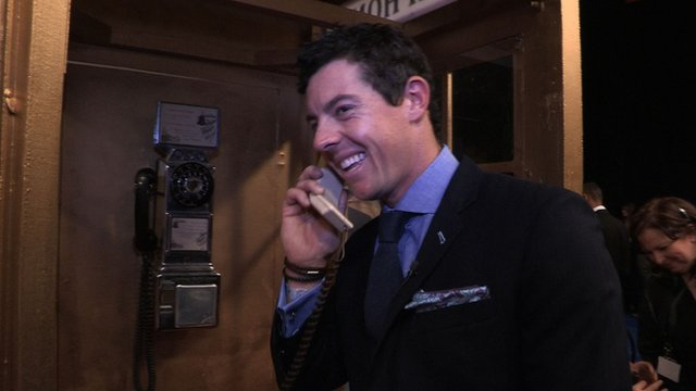 Rory McIlroy on the phone using a payphone