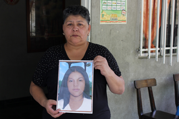 Margarita Restrepo holding a picture of her daughter, Carol