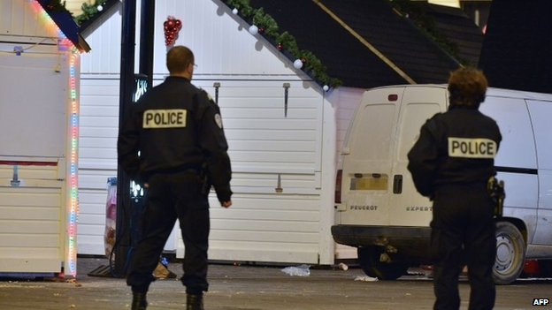 Police stand on the site where a the driver of a van (seen in picture) ploughed into a Christmas market injuring at least ten people before stabbing himself in the western French city of Nantes, 22 December 2014