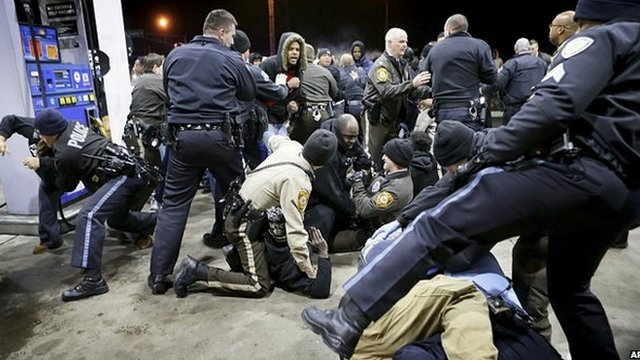Police try to control crowd at Berkeley petrol station. 24 Dec 2014