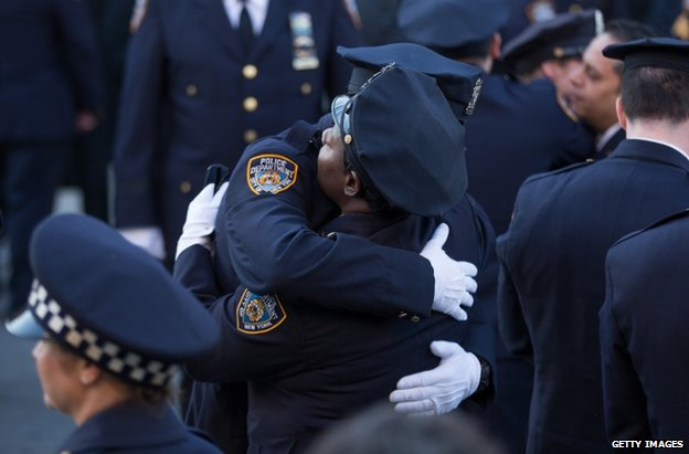Police officers embrace at the funeral in New York, 27 December