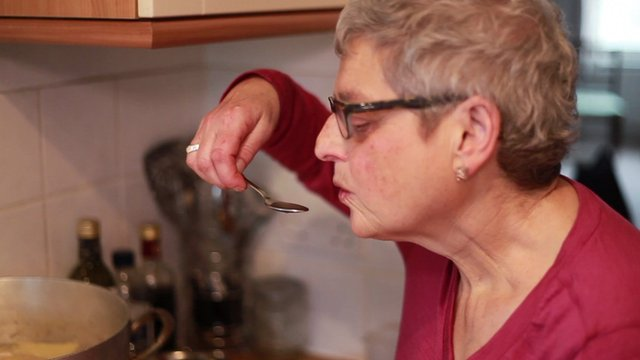Debbie Epstein tasting soup from her mother's pan