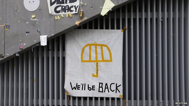 "A poster of an umbrella with the words ""We'll be back"" written underneath is pictured on a wall at the main ""Occupy"" protest site at Admiralty in Hong Kong on 11 December, 2014"