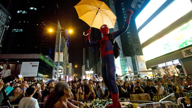 A pro-democracy protester dressed as Spider-man, holding a yellow umbrella, stands on a barricade in the occupied area in the Mong Kok district of Hong Kong, Friday on 24 October, 2014