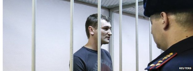 Oleg Navalny, brother and co-defendant of Russian opposition leader and anti-corruption blogger Alexei Navalny, stands inside the defendants cage, during a court hearing in Moscow December 30, 2014.