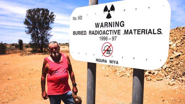 Robin Matthews, caretaker of the Maralinga Nuclear Test Site, stands beside a sign
