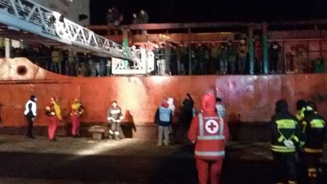 Red Cross personnel wait on the dock as the migrants prepare to leave the ship in Gallipoli, Italy, 31 December