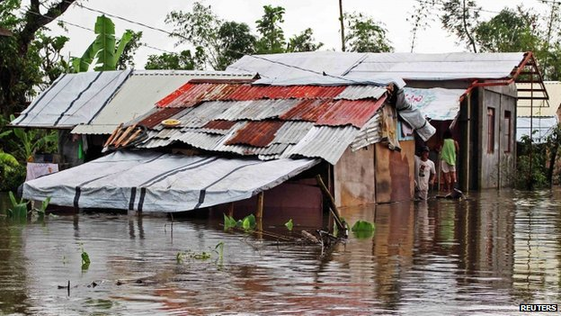 Resident looks out from his home sitting in floodwaters brought on by heavy rains from tropical storm Jangmi, locally called Seniang, in Palo town, Samar province on 30 December 2014.