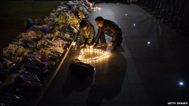 Mourners light candles in the shape of a heart at a makeshift memorial at the site of a stampede on the Bund in Shanghai, China, 1 January 2015