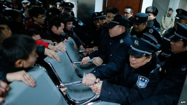 Angry family members clash with security personnel in a hospital where some of the victims of a stampede by new year's revellers were sent in Shanghai, 1 January 2015