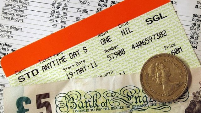 Train ticket, money and a railway timetable