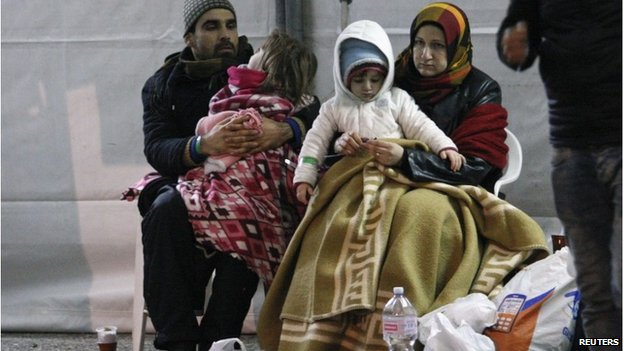 Migrants rest after disembarking from the Ezadeen, 3 January 2015