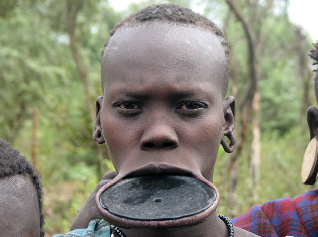 A young Mursi woman with a traditional plate in her lip