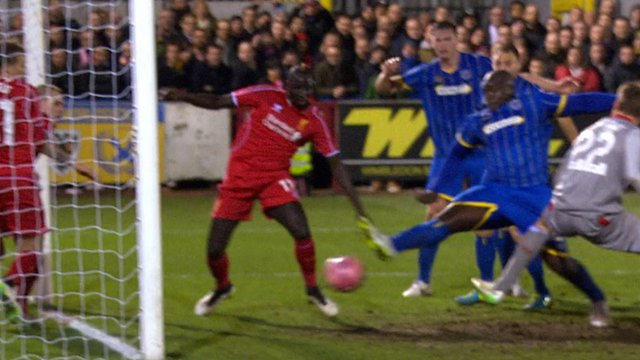 Adebayo Akinfenwa prods home an equaliser for AFC Wimbledon as Liverpool struggle to defend a corner, it's 1-1.