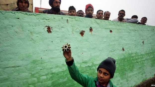 A young Indian villager holds up a piece of a mortar shell allegedly fired from the Pakistani side of the disputed Kashmir, Bainglar village in the Samba sector, some 60 km from Jammu, the winter capital of Kashmir, India, 03 January 2014