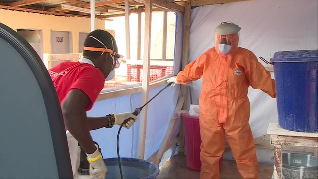 An Ebola healthcare worker being decontaminated