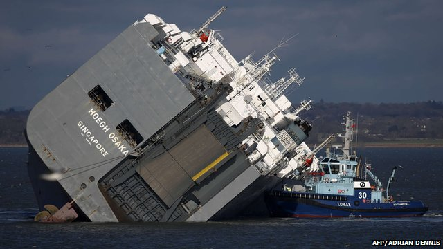 A tug boat alongside the grounded Hoegh Osaka cargo ship in the Solent