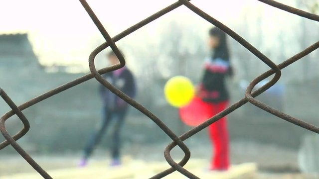 Girls playing with balloons behind barbed wire