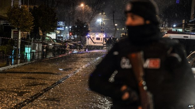 A police officer stands guard along a street leading to a police station where a female suicide bomber was killed on 6 January 2015,