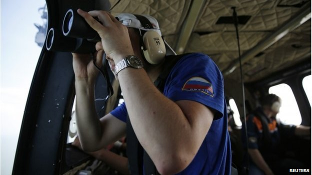 A Russian search team member uses a pair of binoculars to look out the window of a Super Puma helicopter during a search operation for passengers onboard AirAsia Flight QZ8501, off the Java sea, in Indonesia January 7, 2015