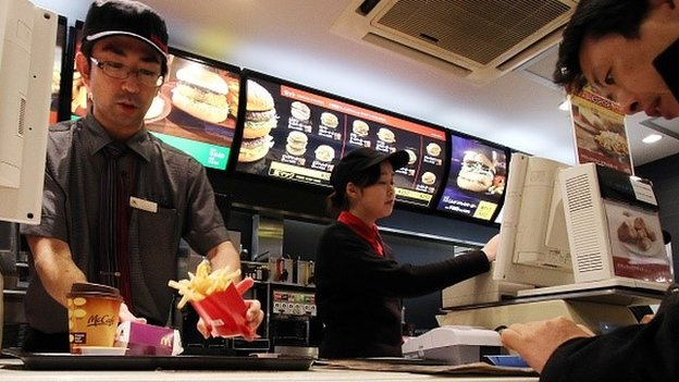 An employee serves French fries to a customer at a McDonald's restaurant in Tokyo on December 16, 2014.