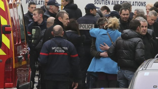 "People hug each other outside the French satirical newspaper Charlie Hebdo""s office, in Paris,on 7 January 2015."