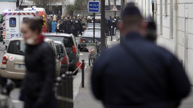 Firefighters and police officers gather in front of the offices of the French satirical newspaper Charlie Hebdo in Paris on 7 January 2015,