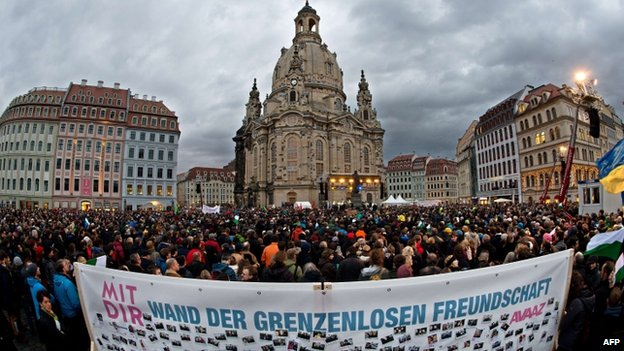 """A banner reading """"Wall of friendship without borders"""" can be seen in the foreground as thousands of people take part in the Dresden rally (10 January 2015)"""