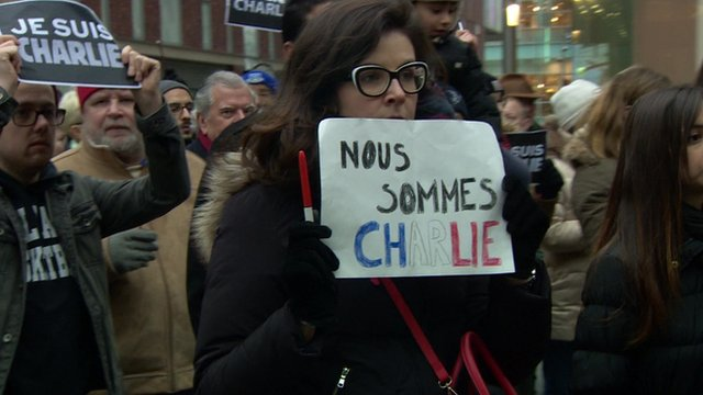 People carried signs and pencils to show solidarity with magazine Charlie Hebdo