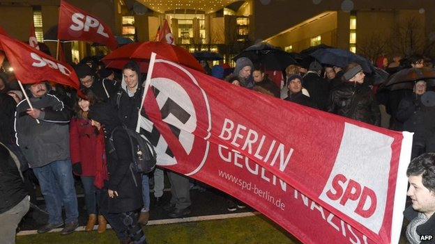 "Members of German social democratic party SPD holds a banner displaying a crossed swastika and reading ""Berlin against Nazis"" during a rally to protest against Germany's anti-Islamisation movement ""Patriotic Europeans Against the Islamisation of the Occident"" PEGIDA, on 12 January 2015 near the Chancellery in Berlin"