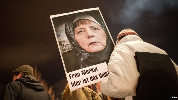 "A participant in a rally with the Anti-Islamic Pegida (Patriotic Europeans against the Islamization of the West) movement holds up a picture of Chancellor Merkel wearing a headscarf written with the words ""Mrs. Merkel - here is the people"" in Dresden, Germany, 12 January 2015"