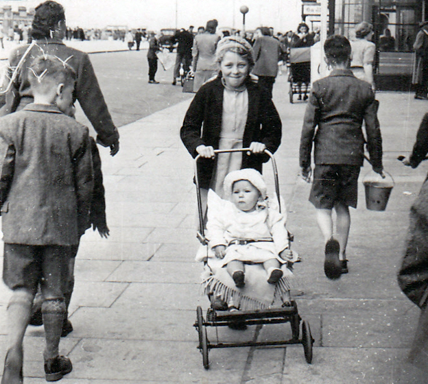 A girl with a young child in a pushchair