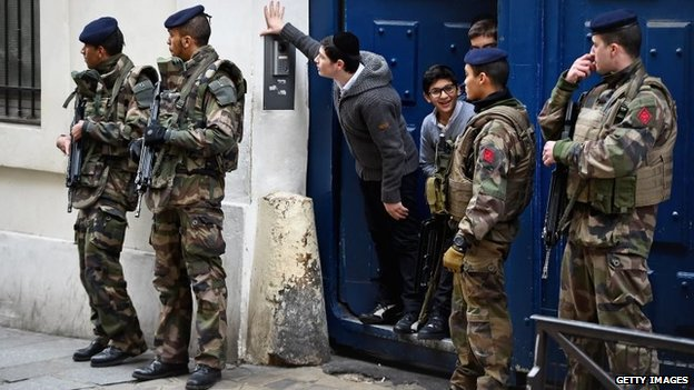Children look out from a doorway as armed soldiers patrol outside a school in the Jewish quarter of the Marais district in Paris, France, 13 January 2015