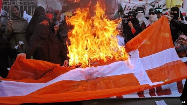 Pakistanis burn a Danish flag during a protest in Lahore against the publication of cartoons depicting the Prophet Muhammad (24 February 2006)