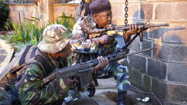 Kenya security personnel take cover outside the Westgate Mall after shooting started inside the mall early Monday morning, on 23 September 2013