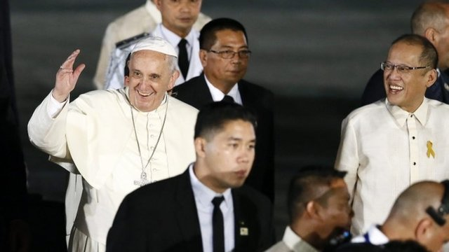 Pope Francis (L) waves next to Philippine President Benigno Aquino III (R)