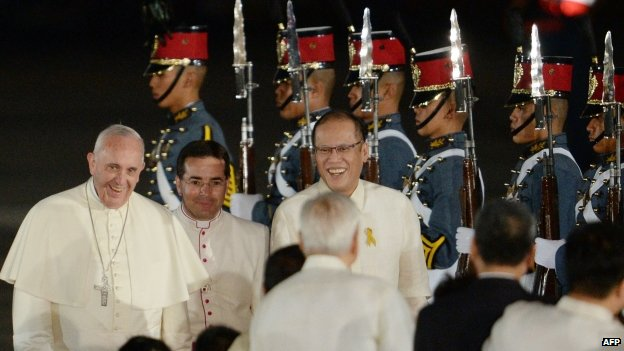 Pope Francis (left) is greeted by children while Philippine President Benigno Aquino (back right) looks on