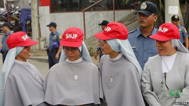 Roman Catholic nuns from Sacred Heart Jesus Parish wait for the motorcade of Pope Francis to pass along a main street in Manila (15 January 2015)