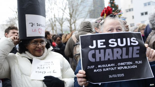 Women hold placards saying Je Suis Charlie at Tignous's funeral