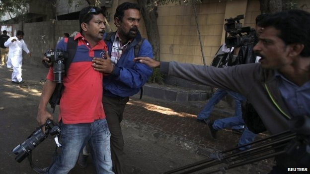 Asif Hassan (L), shot during a protest against satirical French weekly Charlie Hebdo, is helped by a fellow photographer in Karachi January 16,