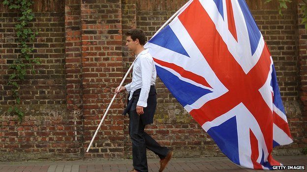 A man carries a large British flag.
