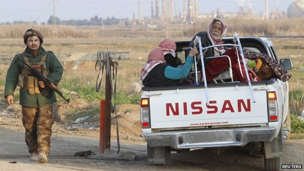 People from the minority Yazidi community, wait inside a truck along a road on the outskirts of Kirkuk